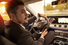 驾驶汽车的英俊的商人 免版税库存图片