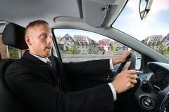 驾驶汽车的震惊商人 库存照片