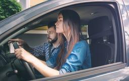 驾驶汽车的驾驶执照考试年轻严肃的妇女感到无经验,注视着紧张公路交通对于信息 免版税库存图片