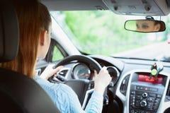 驾驶汽车的年轻深色的妇女 免版税库存图片