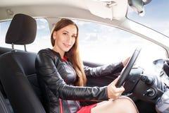 驾驶汽车的年轻美丽的妇女方向盘 库存照片