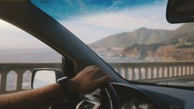 驾驶沿着史诗海岸线路的男性手藏品汽车方向盘美丽的in-car射击在大瑟尔加利福尼亚 影视素材