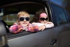 驾驶父亲汽车的女孩和男孩 免版税库存图片