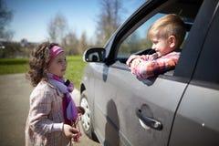 驾驶父亲汽车的女孩和男孩 免版税库存照片
