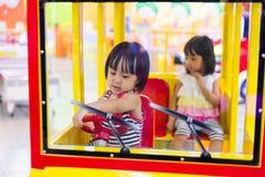 驾驶玩具公共汽车的亚裔中国妹 免版税库存图片