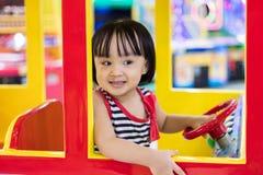 驾驶玩具公共汽车的愉快的亚裔中国小女孩 免版税库存照片