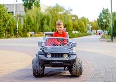 驾驶玩具卡车的逗人喜爱的小男孩 免版税库存图片