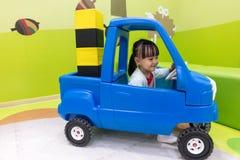 驾驶玩具汽车的亚裔中国小女孩 库存照片