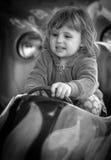 驾驶玩具汽车的女孩 库存照片