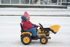 驾驶玩具电挖掘机的小女孩 库存照片