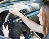 驾驶的十几岁的女孩texting和 库存照片
