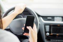 驾驶的妇女发短信和 免版税库存图片