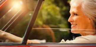 驾驶红色敞篷车的微笑的成熟妇女 库存图片