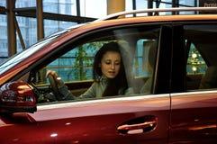 驾驶红色汽车的俏丽的女孩 免版税库存图片