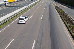 驾驶经常左在一条三线道的高速公路 库存照片