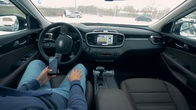 驾驶自动驾驶仪自治汽车的自已 与电话的公司机停放自动地驾驶的一辆汽车 股票视频