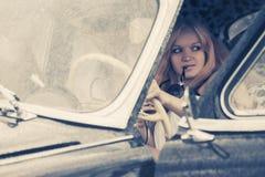 驾驶葡萄酒汽车的年轻时尚夫妇 免版税库存照片