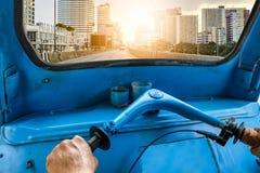驾驶蓝色三轮车tuk-tuk到阳光都市城市 免版税库存图片