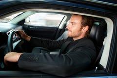 驾驶豪华汽车微笑的年轻人 免版税库存图片