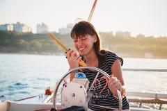 驾驶豪华游艇和使用携带无线电话,热的夏日的镶边衬衣和白色短裤的年轻俏丽的微笑的女孩 库存图片