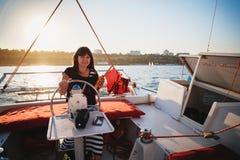 驾驶豪华游艇的礼服的年轻美丽的微笑的女孩在有携带无线电话的在手上,夏天晚上海 免版税库存图片