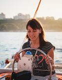 驾驶豪华游艇的镶边衬衣和白色短裤的年轻俏丽的微笑的女孩在海,热的夏日,日落 免版税图库摄影