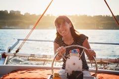 驾驶豪华游艇的镶边衬衣和白色短裤的年轻俏丽的微笑的妇女在海,日落 免版税库存图片
