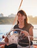 驾驶豪华游艇的镶边衬衣的年轻俏丽的微笑的妇女在海,日落 免版税库存图片