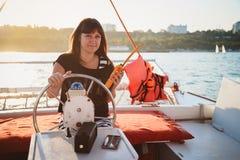 驾驶豪华游艇的黑衬衣的年轻美丽的微笑的女孩在有携带无线电话的在手上,日落海 免版税图库摄影