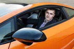 驾驶豪华跑车的愉快的年轻商人 免版税库存照片
