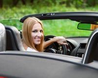 驾驶跑车的白肤金发的少妇 免版税库存图片