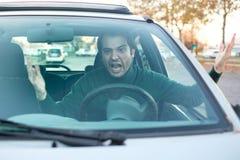 驾驶车的恼怒的年轻人表现出他的路愤怒 库存照片