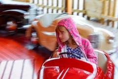 驾驶转盘的集市场所的女孩 免版税库存照片