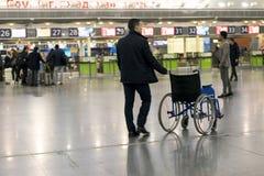驾驶轮椅的机场雇员在机场 所选的重点 库存照片
