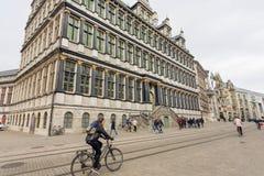驾驶过去哥特式样式城镇厅的自行车的妇女,修建在16世纪 免版税库存照片