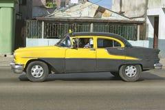 1955驾驶通过哈瓦那古巴街道的黄色Oldsmobile  库存图片