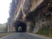 驾驶通过在路的隧道的旅游司机雕刻了在山外面岩石  库存图片