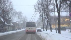 驾驶通过在雪风暴下降的都市城市街道的电车在冬天 4K 影视素材