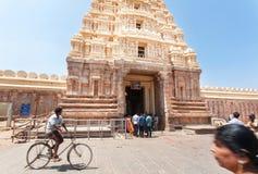 驾驶通过有被雕刻的门gopuram的10世纪Ranganthaswamy寺庙的骑自行车者 免版税库存照片