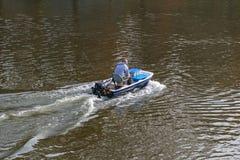驾驶钓鱼的人汽艇在河 库存图片