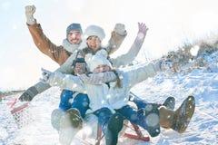 驾驶雪撬和拿着礼物的家庭 免版税库存图片