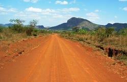 驾驶非洲的红色多灰尘的土路的惊人的背景风景 免版税库存图片