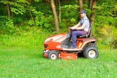 驾驶骑马割草机的花匠在庭院里 免版税库存照片