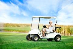 驾驶高尔夫球儿童车的年轻人 免版税库存图片