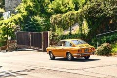 驾驶黄色葡萄酒菲亚特850体育小轿车的年轻人发布了大约1970年在意大利 免版税库存图片