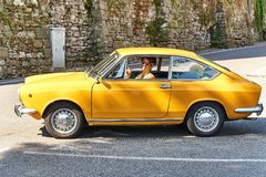 驾驶黄色葡萄酒菲亚特850体育小轿车的年轻人发布了大约1970年在意大利 库存照片
