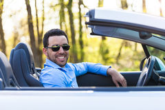 驾驶他新的汽车的黑拉丁美洲的司机 免版税图库摄影