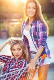 驾驶购物车的两个愉快的美丽的青少年的女孩户外 免版税库存照片