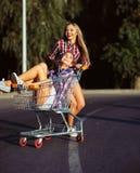 驾驶购物车的两个愉快的美丽的青少年的女孩户外 库存图片