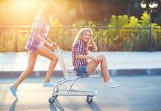 驾驶购物车的两个愉快的美丽的青少年的女孩户外 免版税库存图片